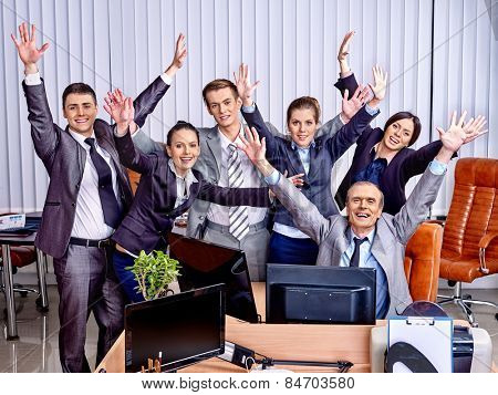 Happy group business people with hand up in office. Venetian blinds background.