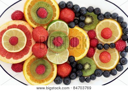 Super food fruit selection in abstract design on a plate over white background.