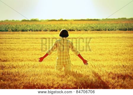 Women in a wheat field at sunset