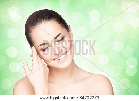 Portrait of young, beautiful and healthy woman over green background. Perfect complexion.