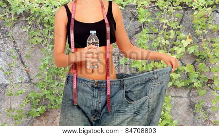 Thin woman stuck in huge pants with a water bottle and a measuring tape