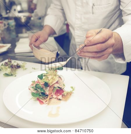 Chef is cooking fish appetizer on professional kitchen, toned image