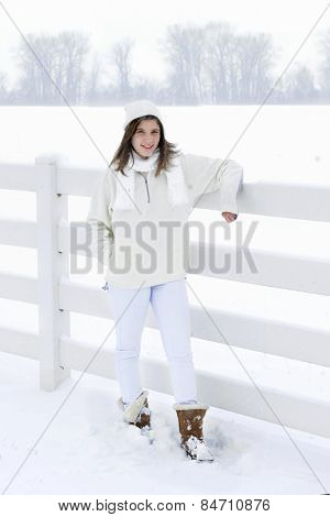 High key image of a pretty teen brunette bundled in white in a snowy white setting.