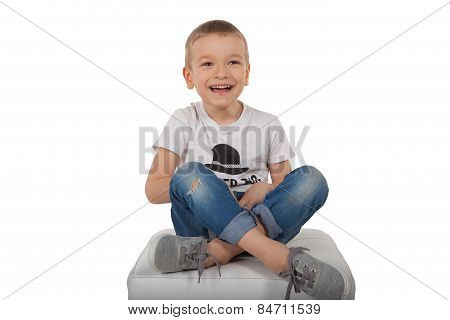 A boy sits on a chair with the camera and laughs