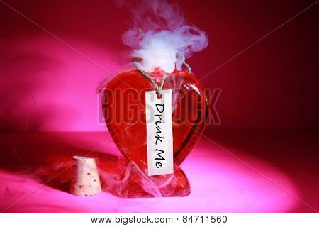 A Genuine LOVE Potion brewed up by a Gypsy, Sorceress, Fortune Teller, Witch, Match Maker, Vixen, or someone who has studied White Magic with the label Drink Me on a hot pink background