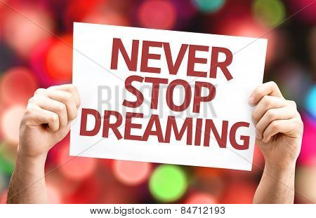 Never Stop Dreaming card with colorful background with defocused lights