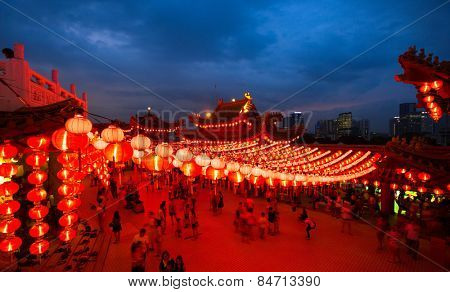 KUALA LUMPUR, MALAYSIA - FEBRUARY 23, 2015: Tourists visit the scenic Thean Hou Temple at night with hundreds of lanterns hung across the courtyard celebrating the lunar Chinese New Year.