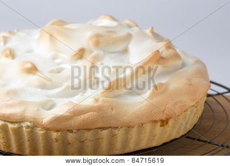 Homemade lemon meringue pie, a classic of European dessert cuisine, on a cooling rack fresh from the oven