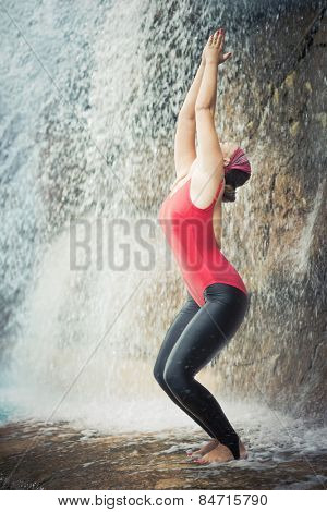 Woman practicing yoga near waterfall. Awkward Pose. Utkatasana