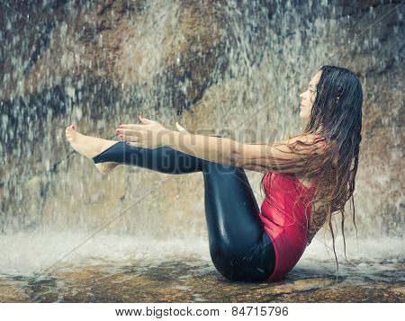 Woman practicing yoga near waterfall. Boat Pose. Navasana