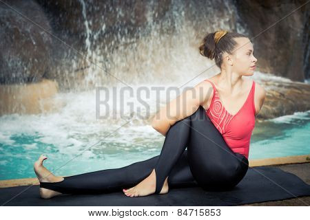 Woman practicing yoga near waterfall. Sage Twist. Marichyasana