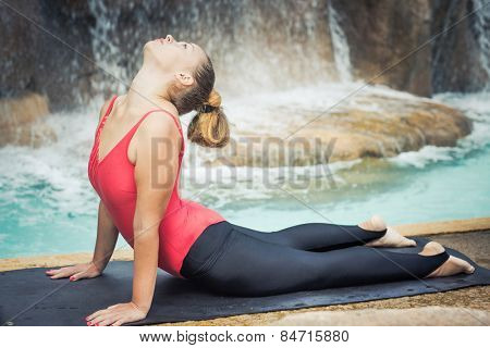 Woman practicing yoga near waterfall. Upward-Facing Dog. Urdhva mukha svanasana