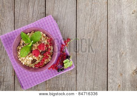 Healty breakfast with muesli and berries. On wooden table with copy space