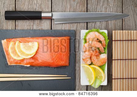 Fresh sea food and kitchen utensils on wooden table