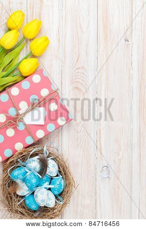 Easter background with blue and white eggs in nest, yellow tulips and gift box. Top view with copy space