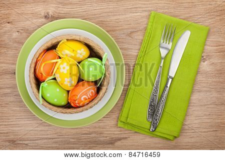 Easter eggs nest on plate over wooden background with silverware