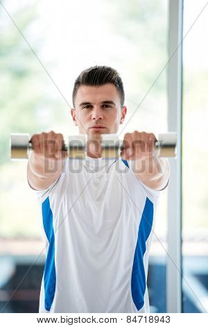 young man in fintess sport club exercise with weights and relaxing