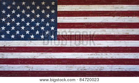 An American or United States flag painted on a wooden plank wall in red, white and blue.