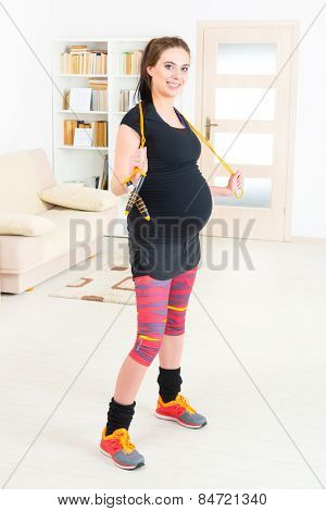 Young pregnant woman exercising with skipping rope or jump rope at home
