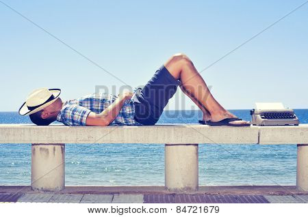 an old typewriter with a blank page and a young man lying down in a street bench near the sea, while is waiting for inspiration