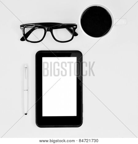 high-angle shot of a table with a pair of black plastic-rimmed eyeglasses, a tablet computer with a copy space, and a cup of coffee