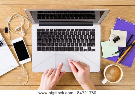 Woman working with laptop placed on wooden desk