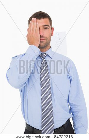 Businessman making an eye test on white background