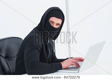 Hacker in balaclava looking at camera on white background
