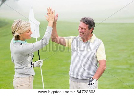 Golfing couple high fiving on a foggy day at the golf course