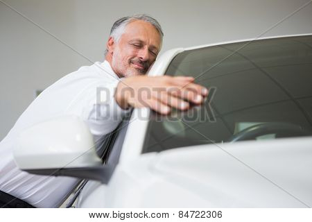 Man hugging on a car at new car showroom