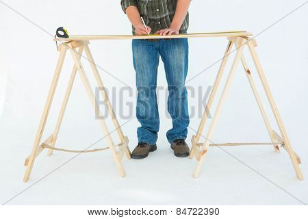 Low section of construction worker marking wooden table against white background