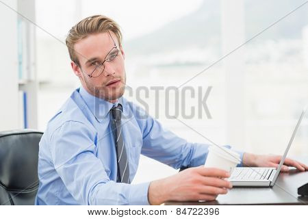 Tired businessman waking up with coffee cup in his office