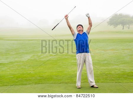 Excited golfer cheering on putting green on a foggy day at the golf course