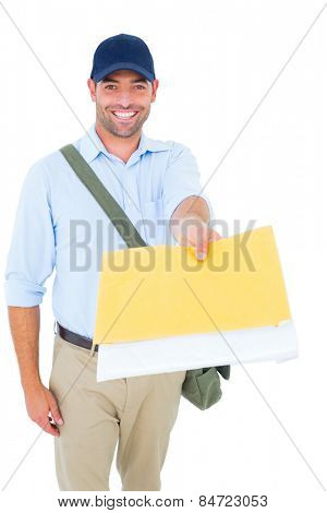 Portrait of happy postman delivering letter on white background