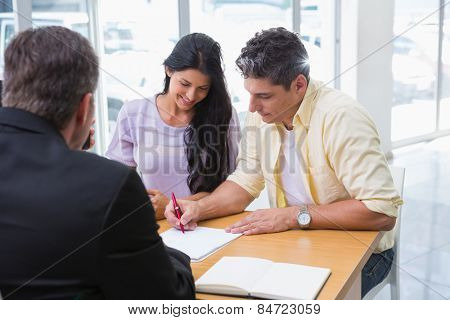 Smiling couple signing a contract at new car showroom