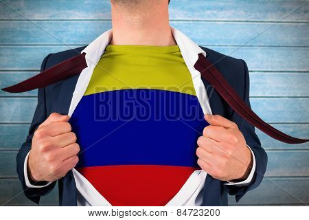 Businessman opening shirt to reveal colombia flag against wooden planks