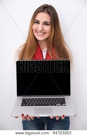 Cheerful beautiful woman showing blank laptop screen