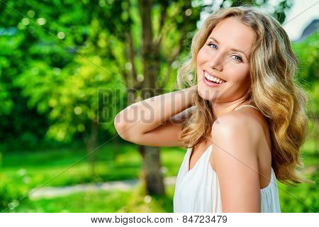 Close-up portrait of a  gorgeous young woman smiling at camera. Outdoor.
