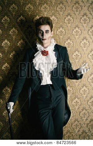Portrait of a handsome male vampire over vintage background. Halloween. Dracula costume.