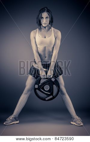 Athletic young woman doing exercise with barbell plate. Fitness sports. Healthcare, bodycare.