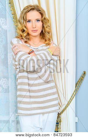 Beautiful woman in casual clothes having a rest at her home. Home interior, furniture. Lifestyle.