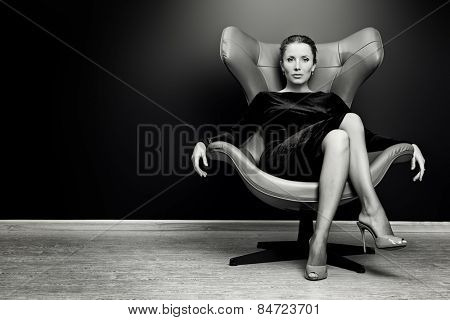 Black and white portrait of a stunning fashionable model sitting in a chair in