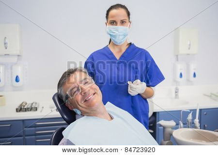 Dentist wearing surgical mask with a smiling patient in dental clinic