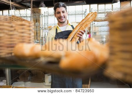 Cheerful waiter holding two baguettes at the bakery