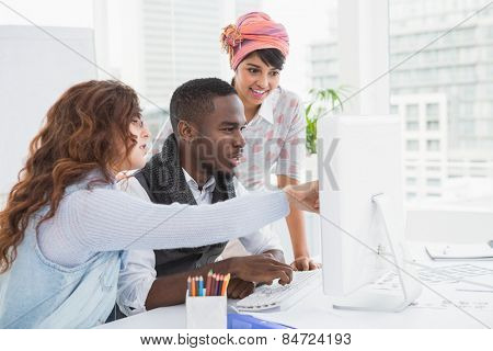 Coworkers pointing computer and interacting in the office
