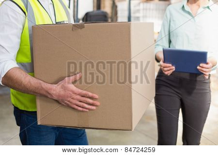 Close up of a warehouse worker carrying box in a large warehouse