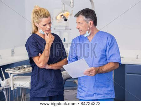 Thoughtful co-workers talking about a file attentively in dental clinic