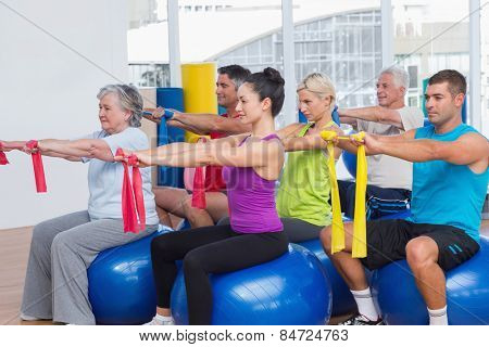 Men and women on fitness balls exercising with resistance bands in gym