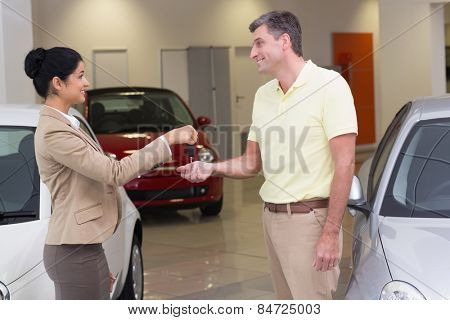 Smiling businesswoman giving car key to happy customer at new car showroom