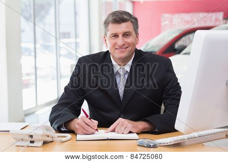 Smiling businessman writing on clipboard at his desk at new car showroom